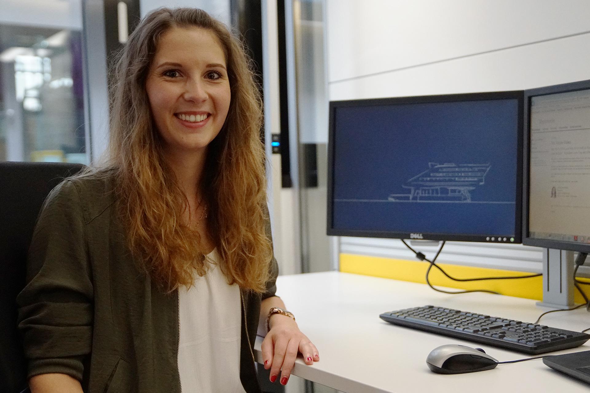 Melanie an ihrem Computerarbeitsplatz mit großen Bildschirmen