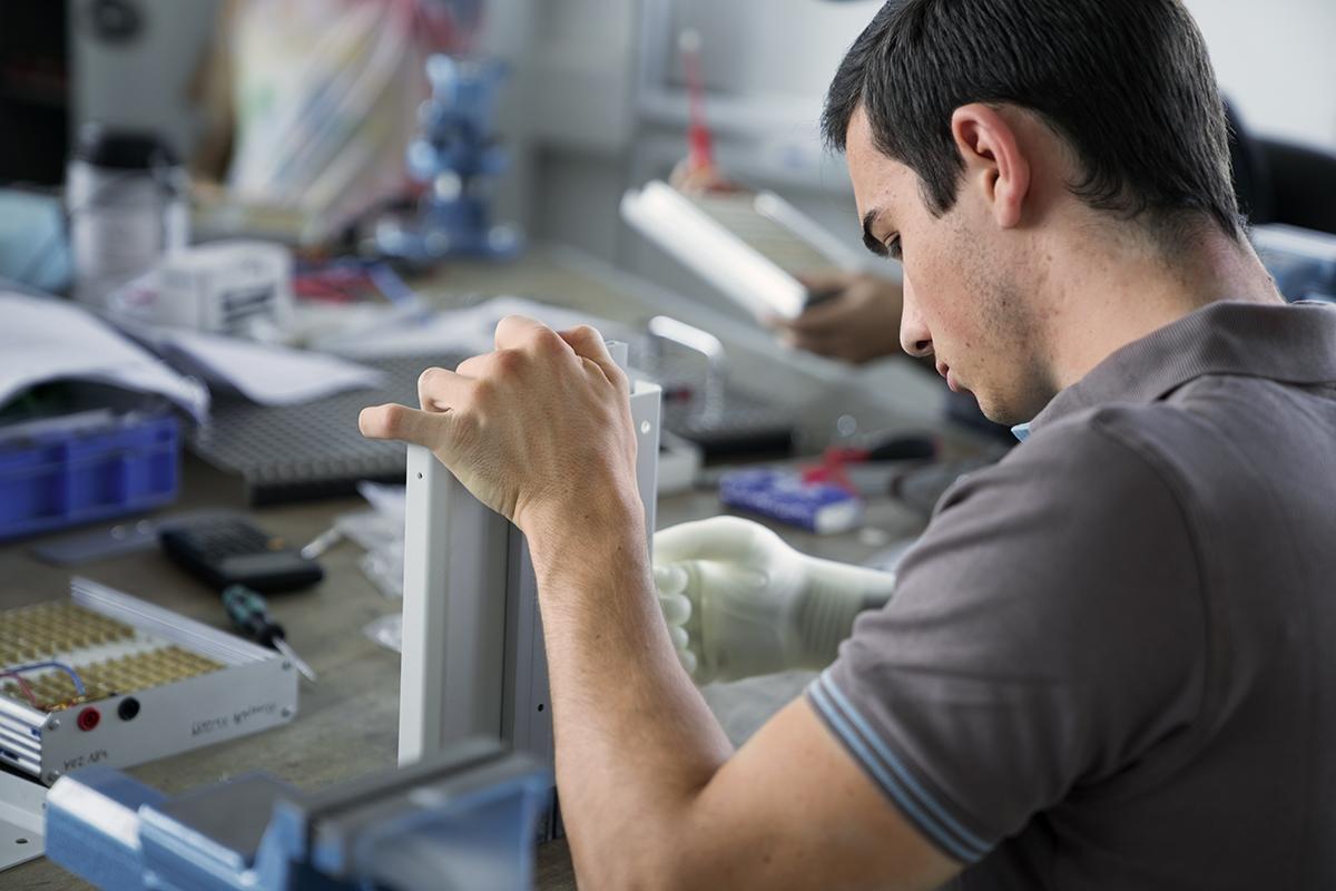 Metalltechniker Alexander sitzt an seinem Arbeitsplatz