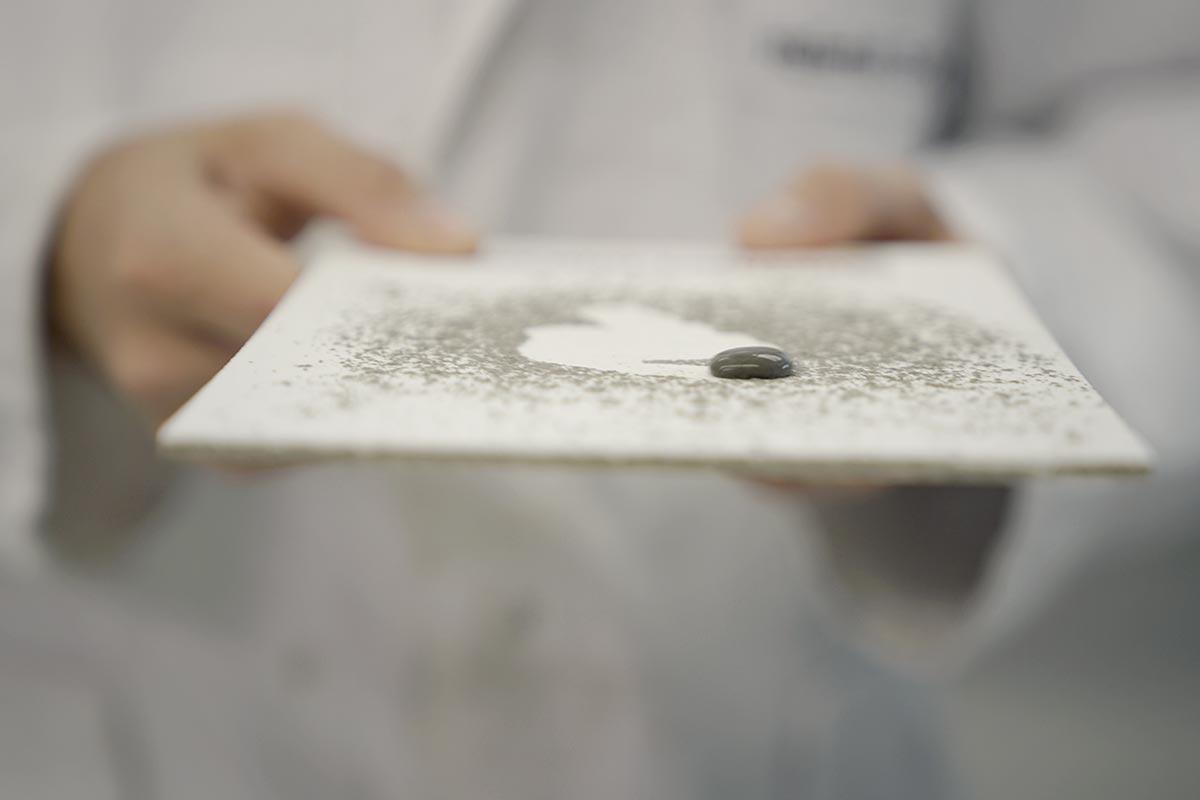 Verschmutzte Platte mit bionischem Anstrick. Schon ein Tropen Wasser entfernt allen Schmutz