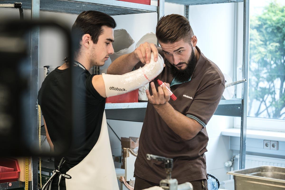 Bei einem Patienten markiert Maximilian mit dem Edding die Bereiche, wo später einmal die Sensoren an der Muskulatur ansetzen