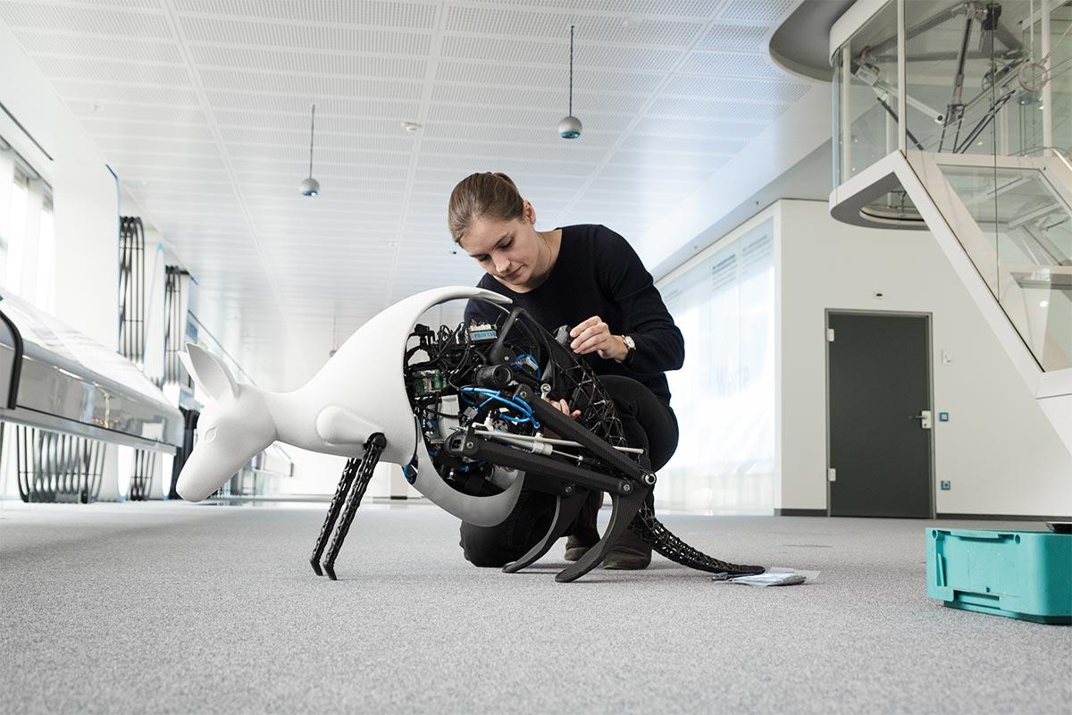 Nadine kniet am Boden und macht das Bionik-Känguru von Festo startklar.