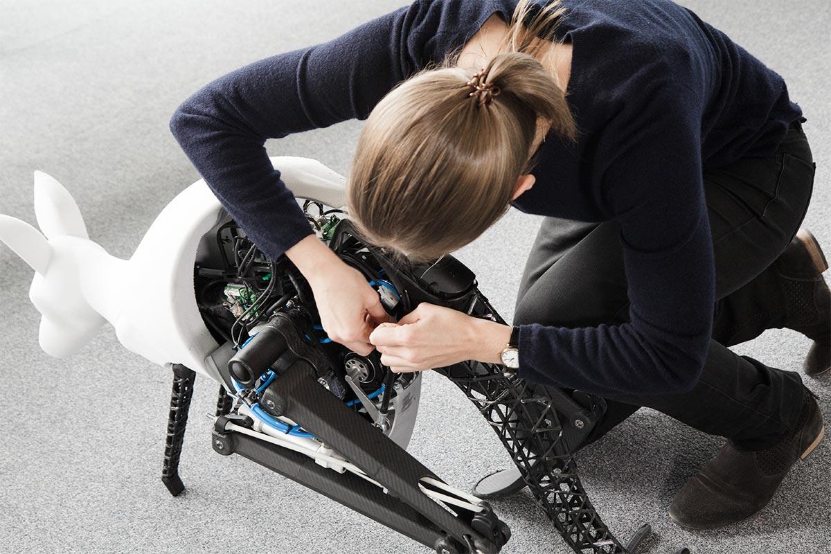 Nadine, in blauem Pulli und schwarzer Hose, beugt sich über das Bionik-Känguru und bereitet alles für die Sprünge vor