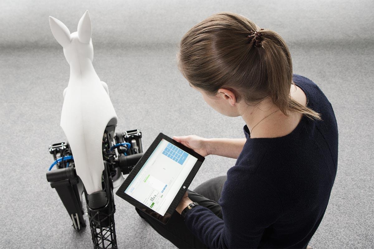Nadine kniet mit einem Tabletcomputer vor dem Bionik-Känguru. Als Informatikerin beschäftigt sie sich mit der Steuerung des Kängurus