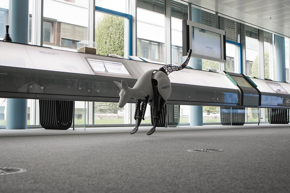 Ein Raum mit Teppich und einer langen Fensterreihe. Das Bionik-Känguru hüpft über den Teppich