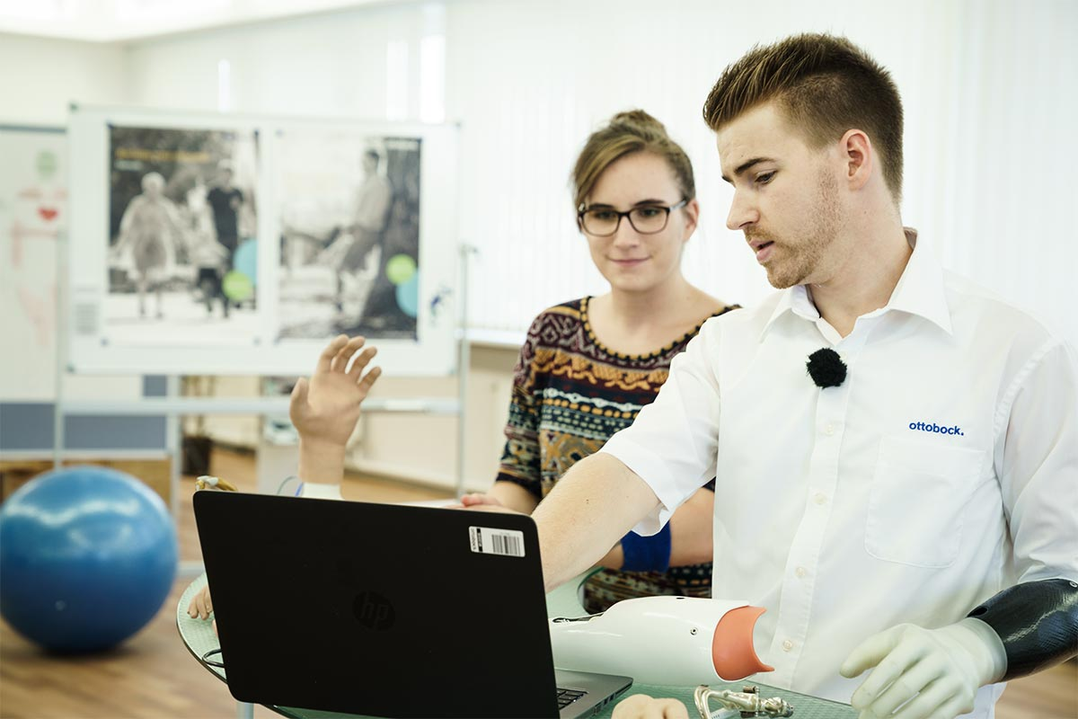 Patrick zeigt einer Kollegin am Laptop welche Anforderungen eine Prothese erfüllen muss