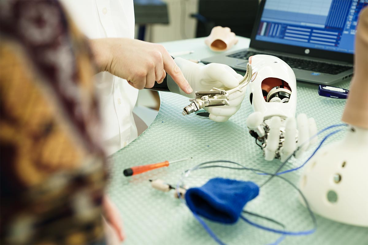 Orthopädietechniker Patrick an seinem Arbeitsplatz mit vielen Teilen von Prothesen