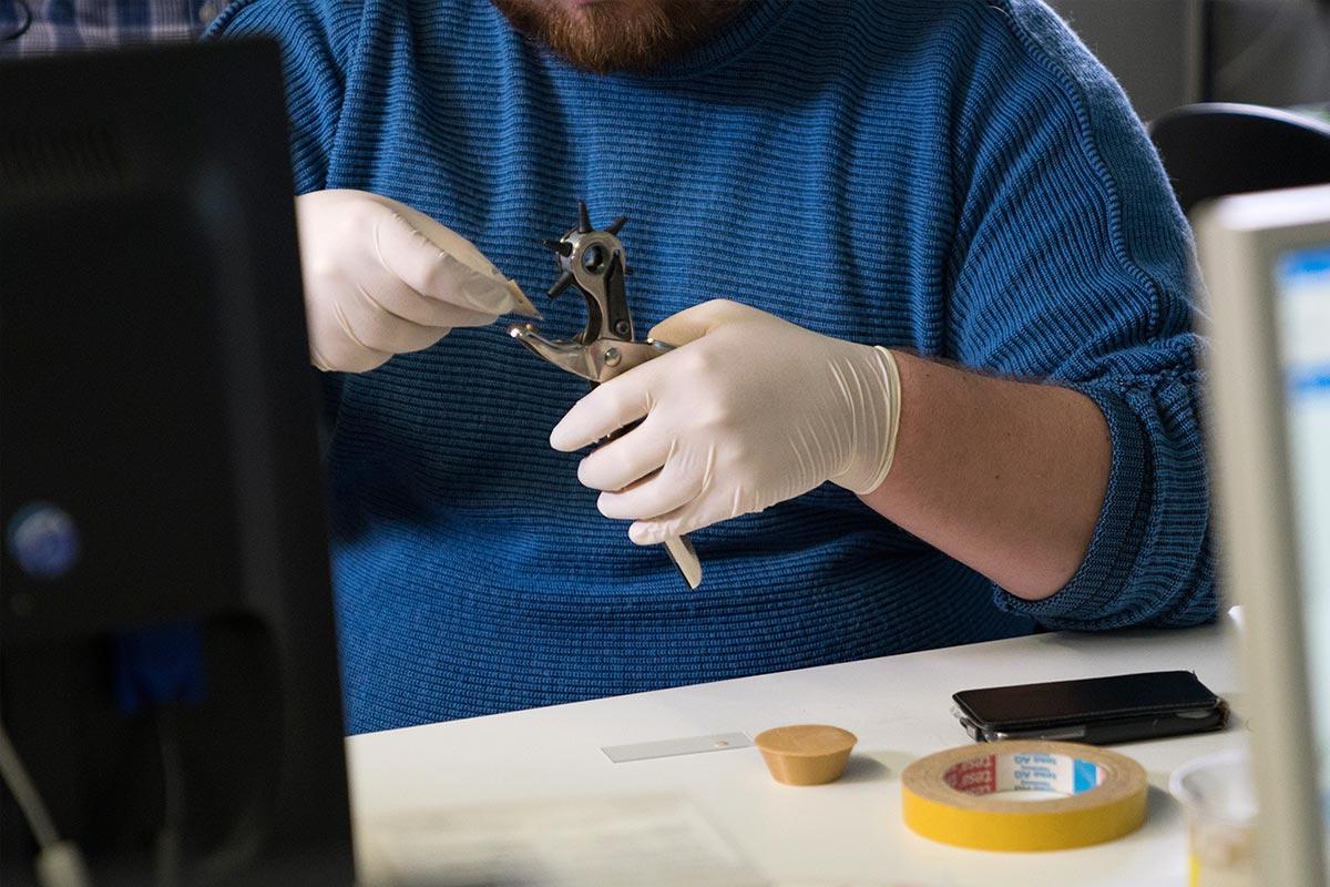 Dennis stanzt mit einer Lochzange Löcher in das sogenannte Geckotape. Damit versucht er die Tragfähigkeit herauszufinden