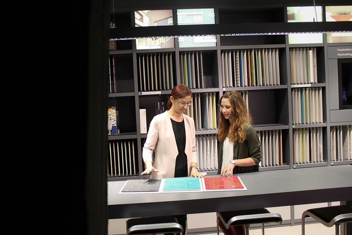 Julia zeigt der Auszubildenden Melanie verschiedene Farb- und Fassadenvarianten die ihr Arbeitgeber, der Farbspezialist Sto, produziert. Auch das gehört zum Dualen Studium