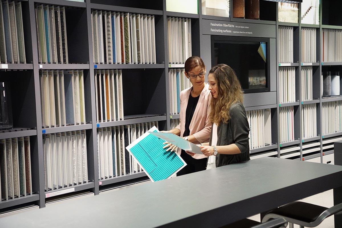 Julia und MElanie stehen vor einer Regalwand mit vielen Fassadenmustern. Julia hat ebenfalls BWL/Industrie studiert und gibt ihr Wissen gerne an die Auszubildenden weiter