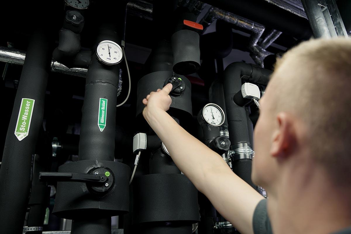 Isolierte Rohre einer Klimaanlage. Leon der Mechatroniker dreht an einem Ventil