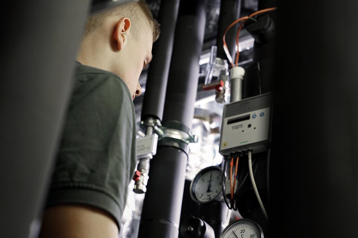 Mechatroniker Leon ist der Herr der Rohre. Er steht zwischen isolierten Rohren mit Ventilen und Termostaten