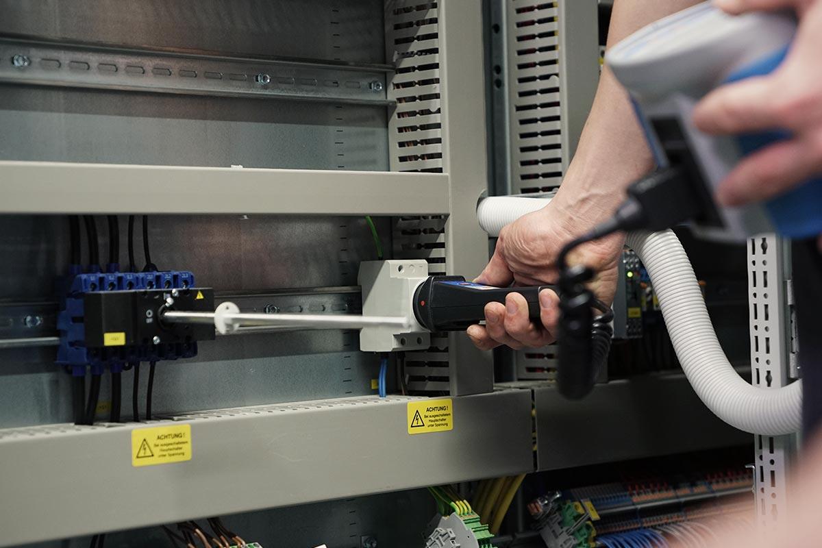 Kabel, Stecker und MEtallleisten. MEchatroniker Leon bei einer Federstromschutzschalter-Prüfung