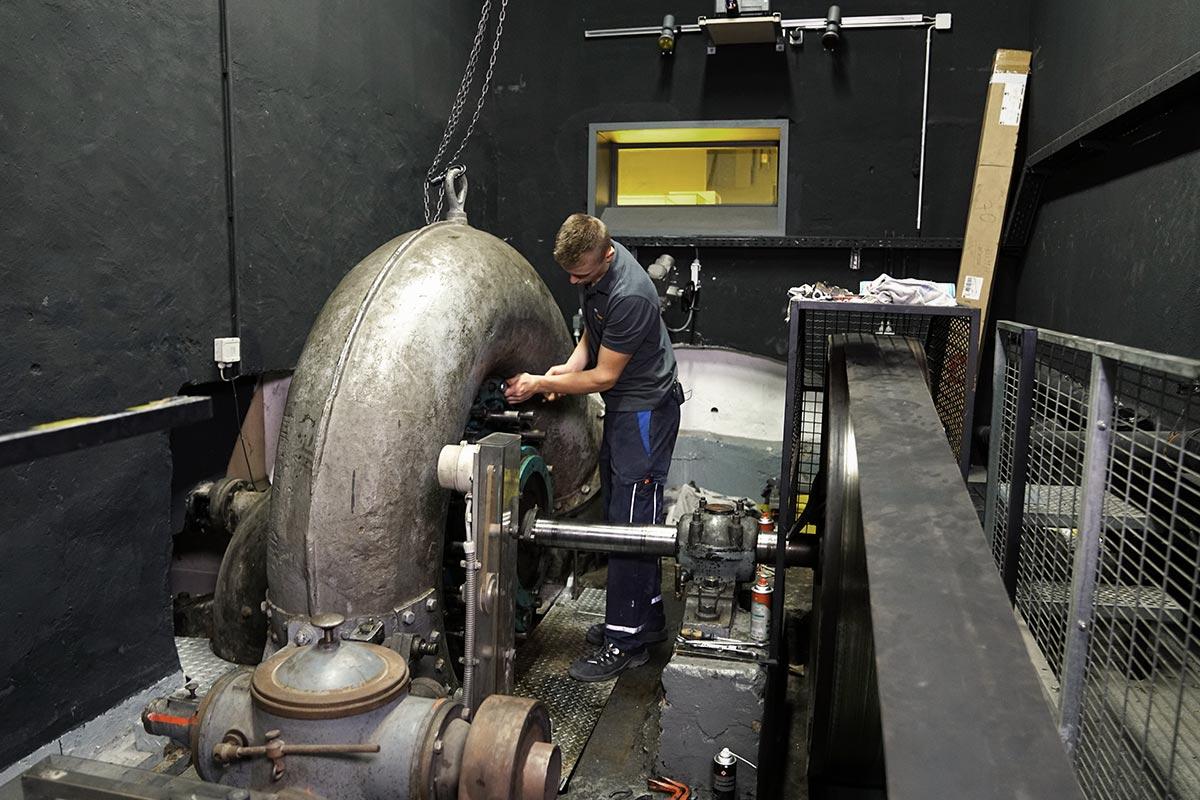 Mechatroniker Leon führt Wartungsarbeiten an einer historischen Wasserturbine durch. Auch das gehört zu seinem Beruf