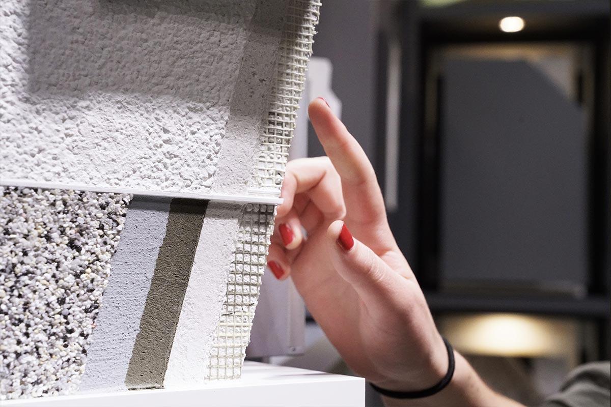 Melanie zeigt mit ihrem Finger auf ein Fassadenelement. So ein Wandputz muss heute richtig viel können