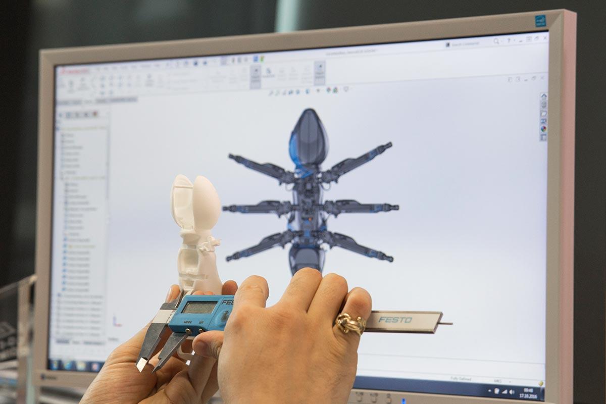 Mit einem Messschieber vermisst Sebastian den im 3D-Druckverfahren ausgedruckten des Ameisenkörpers und vergleicht die Maße mit der Konstruktionszeichnung an seinem Computer