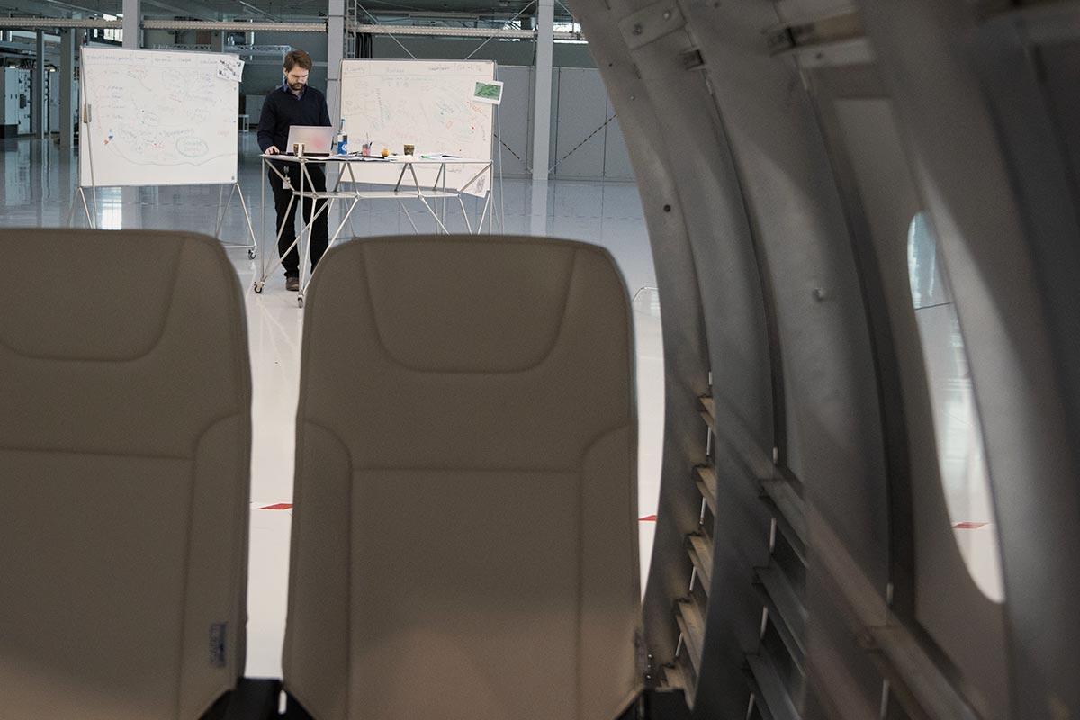 Blick durch das Innenraummodell eines Flugzeuges auf Sebastian, der vor zwei Flipcharts an einem Rolltisch mit Laptop darauf steht.