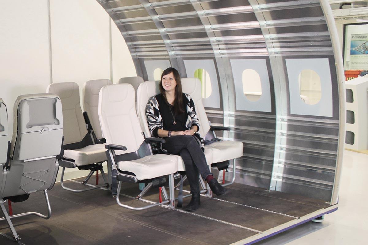 Christine sitzt in einem Innenraummodell eines Airbus, das für die Luftfahrtforschung benötigt wird