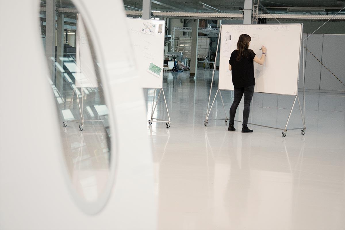 Christine steht vor einer großen Flipchart in einer Halle
