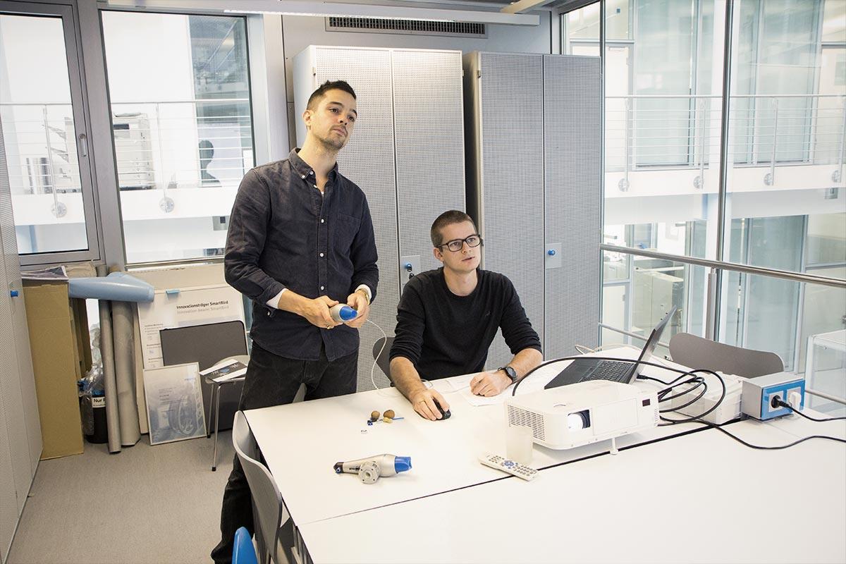 Maschinenbauer Mart und Industriedesigner Sebastian stimmen sich an Marts Arbeitsplatz ab