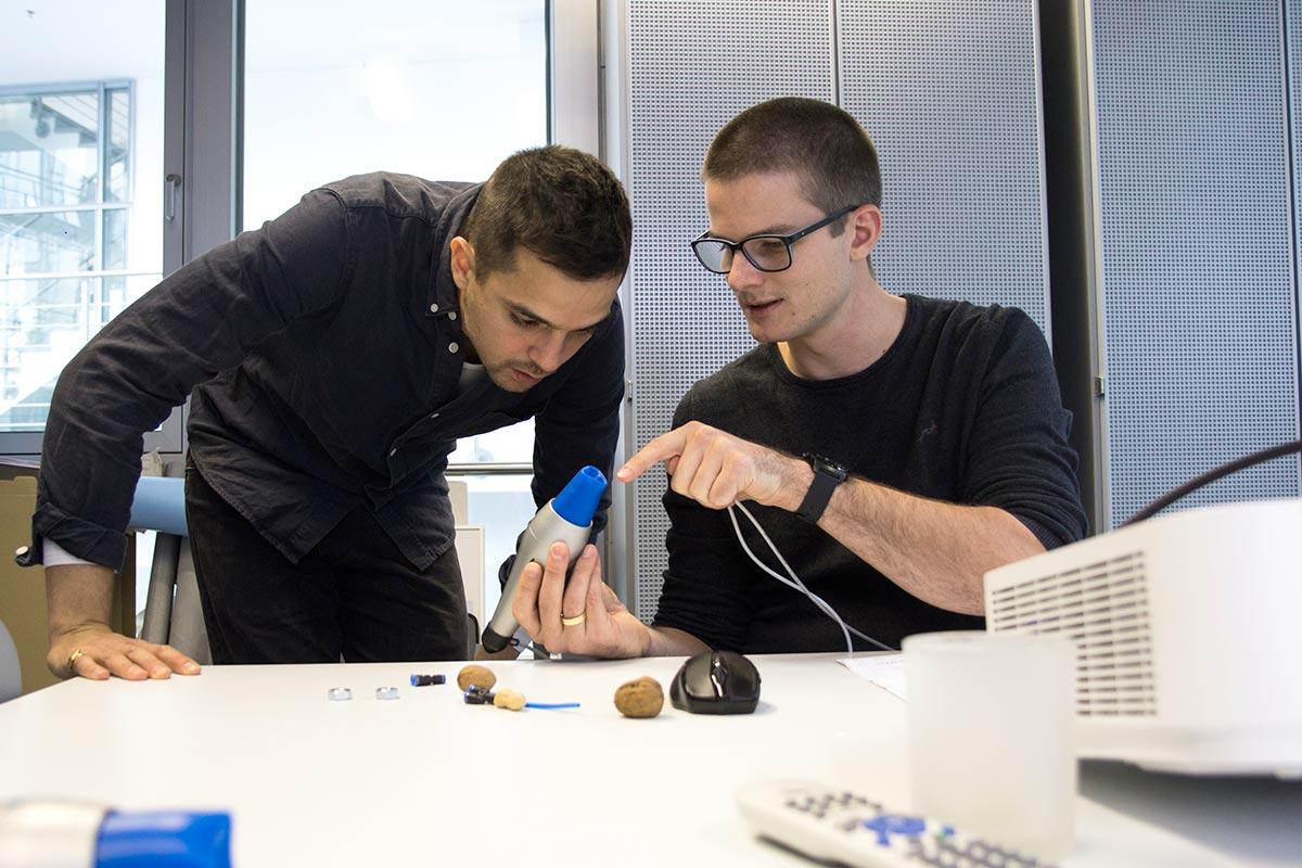 Mart zeigt einem Kollegen, wie der FlexShapeGripper, der das Greifprinzip der Chamäleon-Zunge nutzt, funktioiert
