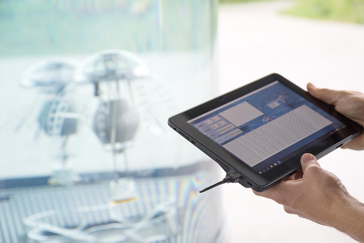 Zwei Hände halten einen Tabletcomputer. Im Hintergrund sind verschwommen Roboterquallen zu  erkennen