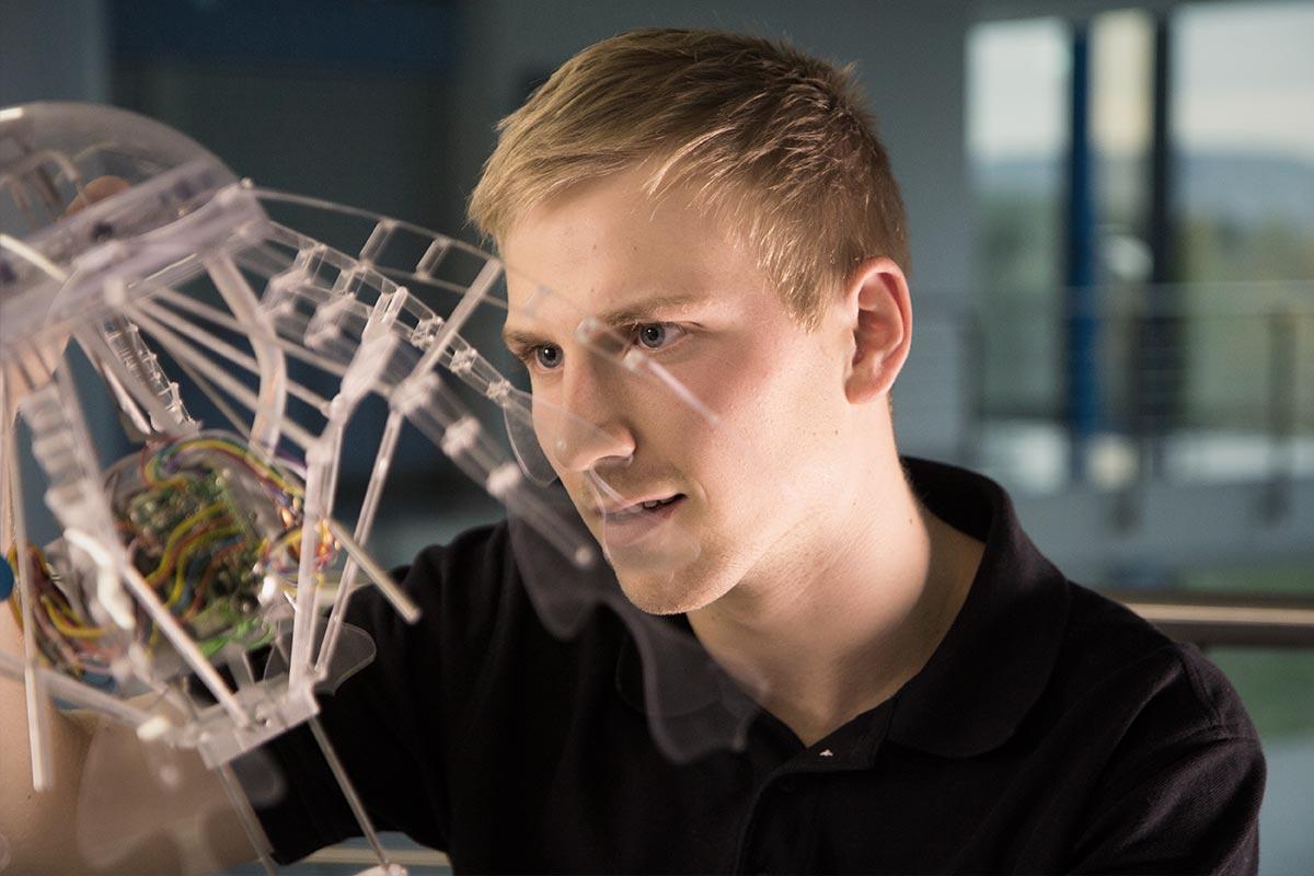 """Mechatroniker MIcha hält die High-Tech Robo-Qualle """"AquaJellie"""" vor sich"""