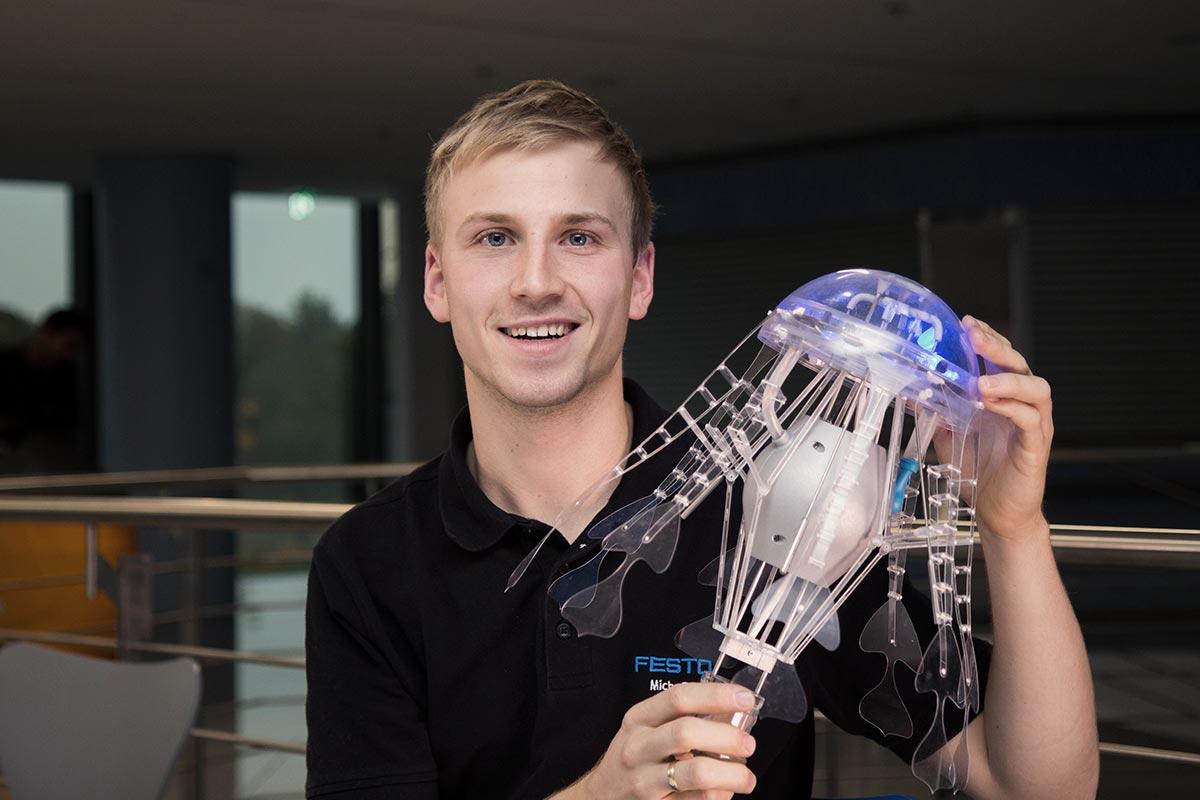 """Mechatroniker Micha hält eine blau leuchtende """"AquaJellie"""" vor sich. Er ist stolz darauf Teil dieses Projektes zu sein"""