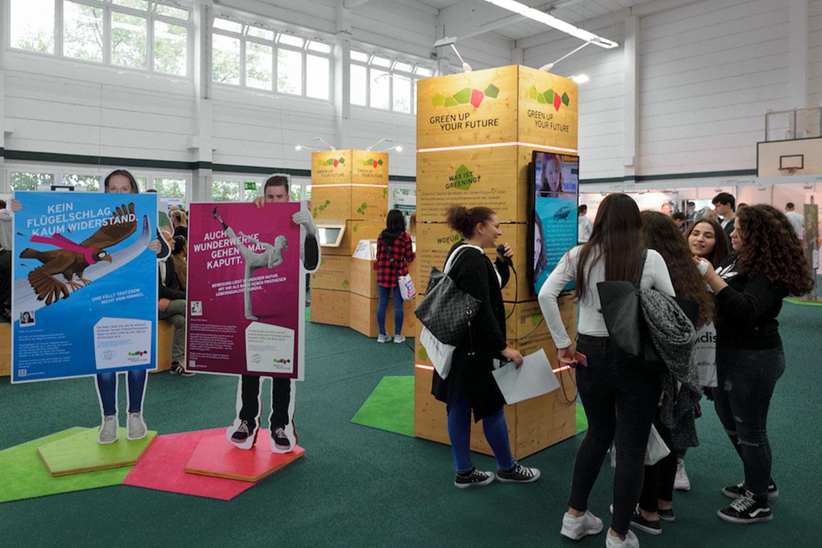 Jugendliche interagieren mit den verschiedenen Modulen der Austellung in einer Sporthalle