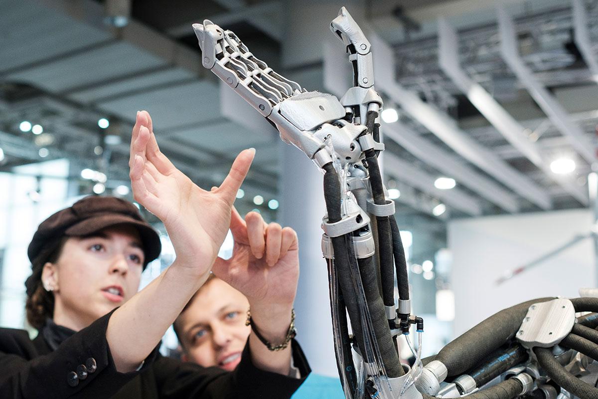 Jugendliche betrachten Arics Arm auf der Ausstellung