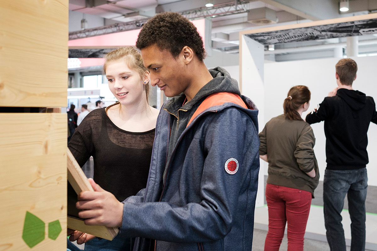 Jugendliche interagieren mit einem Touchscreen der Austellung