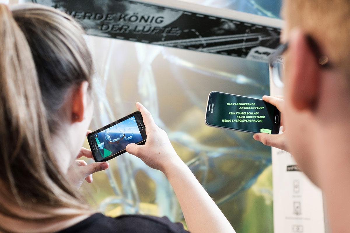 Jugendliche benutze ihre Smartphones um die Austellung in der Augmented Reality zu erleben