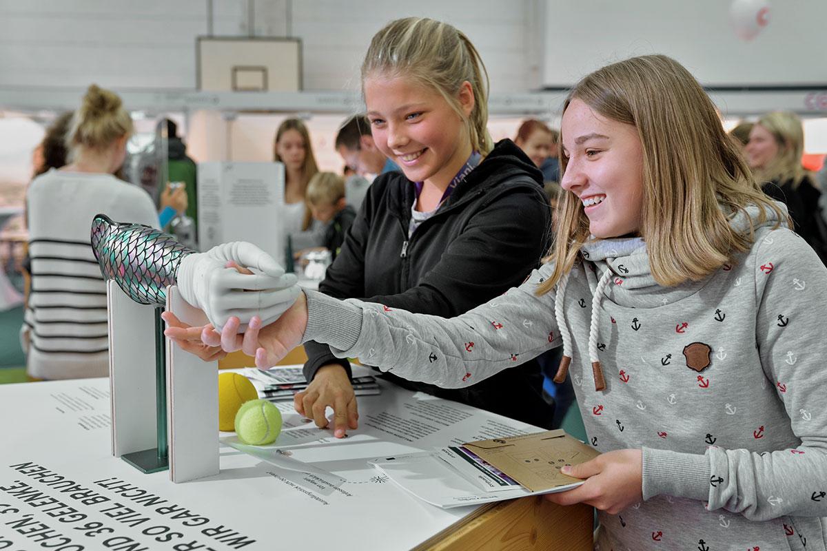 Jugendliche interagieren mit dem Austellungsstück einer Armprothese